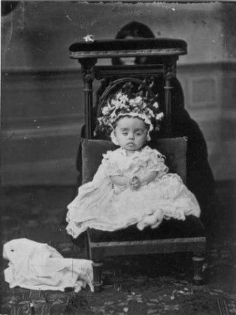 Человек за стулом держит голову ребенка.