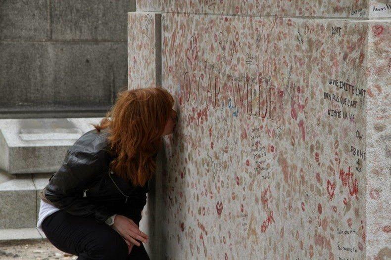 девушка целует памятник на могиле Оскара Уайльда